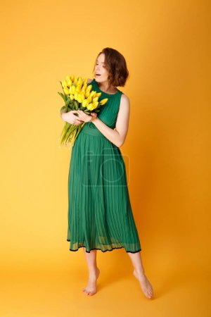 Photo for Pretty woman in green spring dress looking at bouquet of yellow tulips in hands isolated on orange - Royalty Free Image