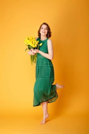 Photo pour Jolie jeune femme en robe verte avec bouquet de tulipes printanières jaunes isolées sur orange - image libre de droit