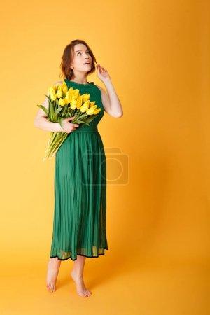 Photo pour Songeuse femme en robe verte avec bouquet de Tulipes jaunes isolées sur orange - image libre de droit