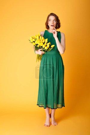 Photo pour Songeuse jeune femme en robe verte avec bouquet de Tulipes jaunes vous cherchez loin isolé sur orange - image libre de droit