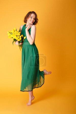 Photo pour Belle jeune femme en robe avec bouquet de tulipes printemps isolé sur orange - image libre de droit