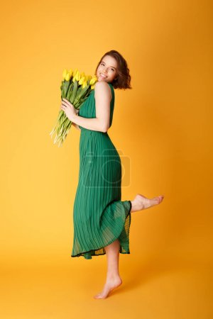 Photo pour Vue latérale de la femme heureuse en robe verte avec bouquet de tulipes jaunes de printemps dans les mains isolées sur orange - image libre de droit
