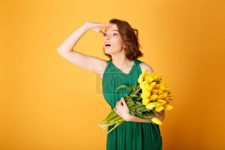 Photo for Portrait of young woman with bouquet of yellow tulips looking away isolated on orange - Royalty Free Image