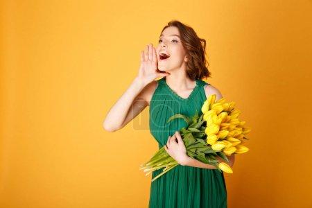 Photo pour Portrait de jeune femme avec bouquet de Tulipes jaunes criant isolé sur orange - image libre de droit