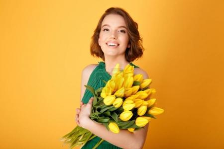Photo pour Portrait de femme souriante avec bouquet de Tulipes jaunes isolées sur orange - image libre de droit