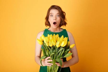 Photo pour Portrait de femme choqué avec bouquet de Tulipes jaunes isolées sur orange - image libre de droit