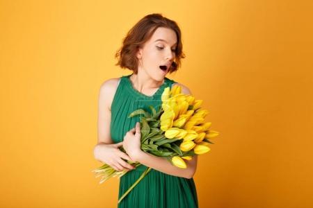 Photo pour Portrait d'une femme surprise en regardant bouquet de Tulipes jaunes isolées sur orange - image libre de droit