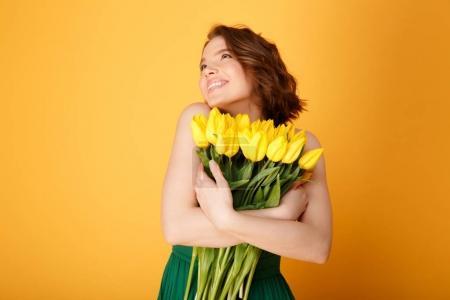 Photo pour Portrait de femme heureuse hugging bouquet de Tulipes jaunes isolées sur orange - image libre de droit