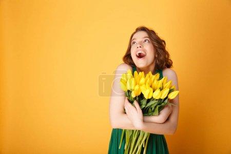 Photo pour Portrait de femme excitée avec bouquet de Tulipes jaunes isolées sur orange - image libre de droit