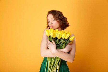 Photo pour Portrait de jeune femme avec bouquet de Tulipes jaunes isolées sur orange - image libre de droit