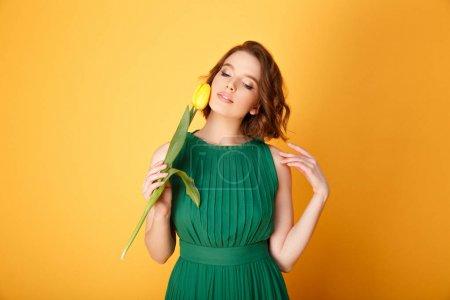Photo pour Portrait d'une femme tendre dans une robe verte avec tulipe jaune isolé sur orange - image libre de droit