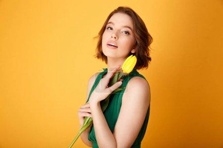 Photo pour Portrait de la belle femme en robe verte avec tulipe jaune isolé sur orange - image libre de droit