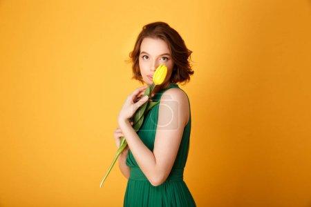 Photo pour Portrait de jolie femme en robe verte tenant tulipe jaune isolé sur orange - image libre de droit
