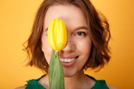 Photo pour Femme souriante, couvrant les yeux avec tulipe jaune isolé sur orange - image libre de droit