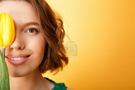 Photo pour Vue partielle de femme souriante avec tulipe jaune isolé sur orange - image libre de droit