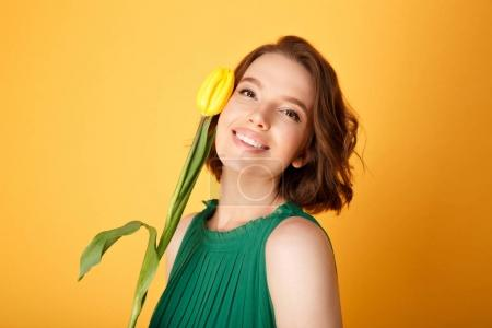 portrait of smiling woman with yellow tulip isolated on orange