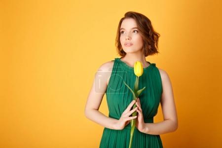 Photo pour Portrait de femme pensive en robe verte tenant tulipe jaune isolé sur orange - image libre de droit