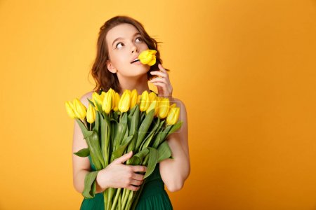 portrait of pensive woman with tulip in mouth and bouquet of yellow tulips isolated on orange