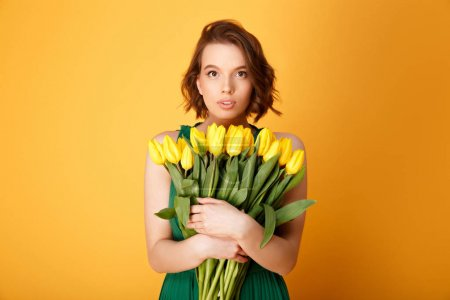 portrait of beautiful woman with bouquet of yellow tulips isolated on orange