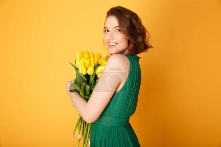 Photo pour Vue de côté de femme joyeuse avec bouquet de Tulipes jaunes isolées sur orange - image libre de droit