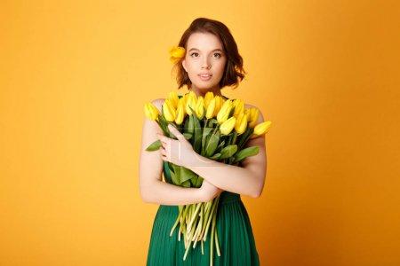 Photo pour Portrait de jolie jeune femme avec bouquet de Tulipes jaunes isolées sur orange - image libre de droit