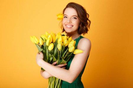 Photo pour Portrait d'une femme jeune heureux avec bouquet de tulipes printemps isolé sur orange - image libre de droit