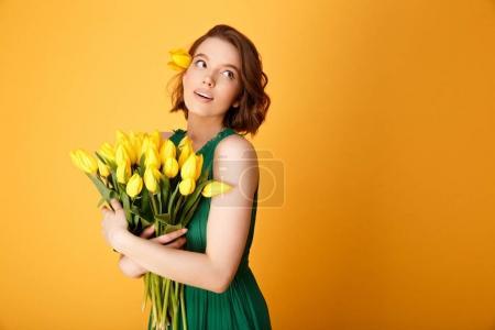 Photo pour Portrait de jeune femme jolie bouquet de Tulipes jaunes isolées sur orange - image libre de droit