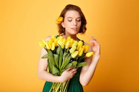 Photo pour Portrait de jeune femme regardant bouquet de tulipes jaunes à la main isolé sur orange - image libre de droit