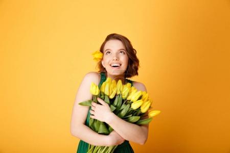 Photo pour Portrait de femme joyeuse avec bouquet de Tulipes jaunes printemps en handsisolated sur orange - image libre de droit