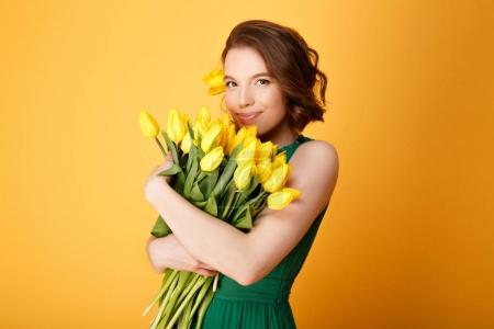portrait of attractive woman with bouquet of yellow tulips in hands isolated on orange