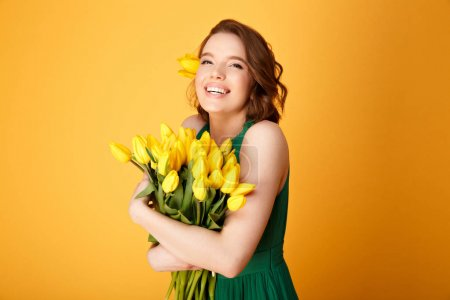 Photo for Portrait of happy woman in green dress with bouquet of yellow tulips isolated on orange - Royalty Free Image