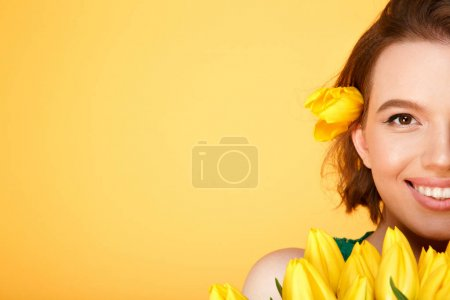 Photo for Partial view of smiling woman with bouquet of yellow tulips isolated on orange - Royalty Free Image