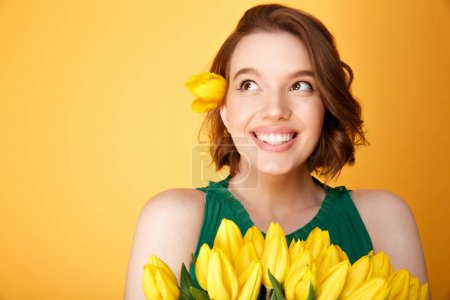 portrait of dreamy woman with bouquet of yellow tulips isolated on orange