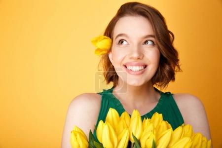 Foto de Retrato de mujer de ensueño con ramo de tulipanes amarillos aislados en naranja - Imagen libre de derechos