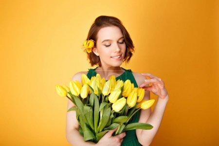 Photo pour Portrait de jolie femme regardant bouquet de Tulipes jaunes en main isolés sur orange - image libre de droit