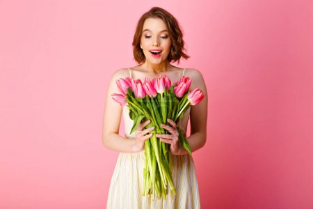 Photo for Portrait of surprised woman looking at bouquet of pink tulips in hands isolated on pink - Royalty Free Image