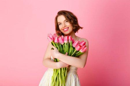Photo pour Femme souriante avec bouquet de tulipes roses, regardant la caméra isolée sur rose - image libre de droit
