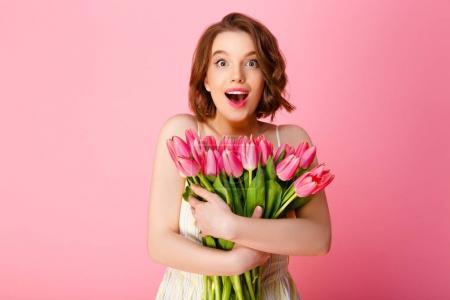 Photo pour Femme excitée avec bouquet de tulipes roses regardant la caméra isolée sur rose - image libre de droit