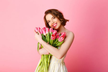 Photo for Attractive smiling woman hugging bouquet of pink tulips isolated on pink - Royalty Free Image