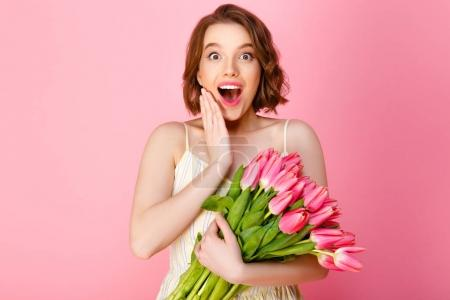 surprised woman with bouquet of spring tulips isolated on pink