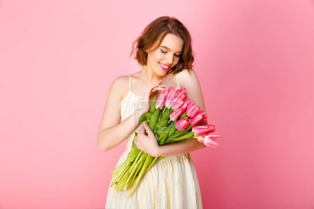 portrait of beautiful woman holding bouquet of pink tulips isolated on pink