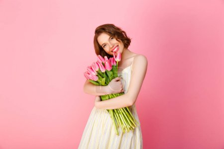 Photo for Cheerful woman hugging bouquet of pink tulips isolated on pink - Royalty Free Image
