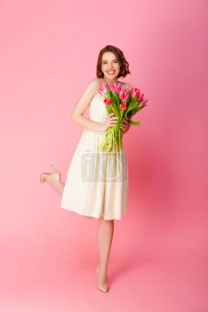 Photo for Attractive smiling woman with bouquet of spring tulips isolated on pink - Royalty Free Image