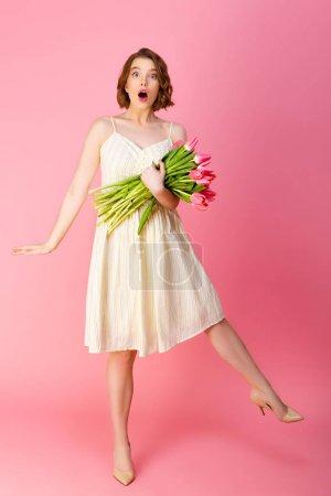 Photo pour Jeune femme émotive en robe blanche avec bouquet de tulipes printemps rose isolé sur rose - image libre de droit