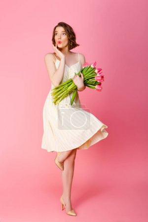 Photo for Beautiful woman in white dress with bouquet of pink tulips isolated on pink - Royalty Free Image