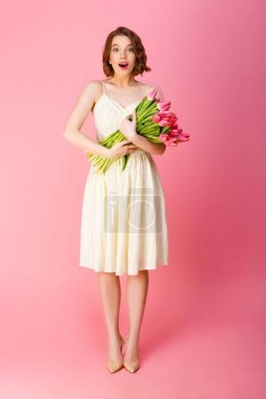 Photo pour Femme émotionnelle avec bouquet de tulipes roses regardant la caméra isolée sur rose - image libre de droit