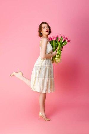 Photo pour Vue latérale de jeune femme en robe blanche avec bouquet de tulipes roses isolées sur rose - image libre de droit
