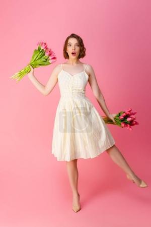 Photo pour Femme choquée en robe blanche avec des bouquets de fleurs de printemps isolé sur rose - image libre de droit