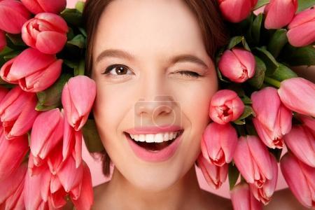 Photo pour Tête de jeune femme, clin d'oeil à la caméra et rose tulipes autour - image libre de droit