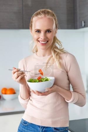 beautiful young woman eating fresh vegetable salad and smiling at camera